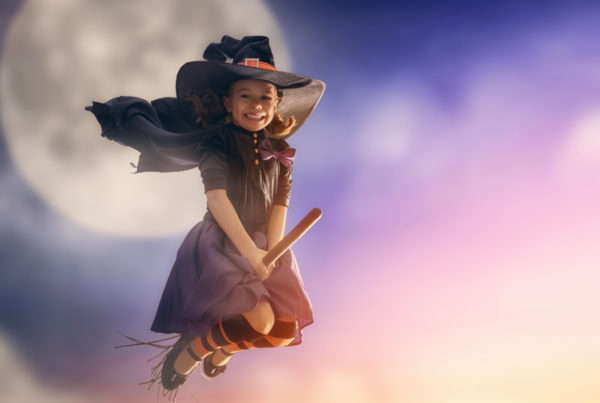 Cute little girl dressed as a witch flying on a broomstick in front of the moon to celebrate Halloween content marketing