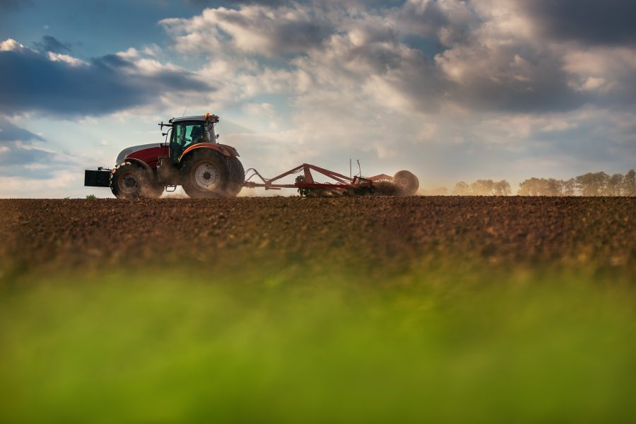 5 days for good, Supporting Food Security in Canada, image of a tractor plowing a field in Canada, beautiful sky and green in the foreground