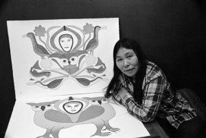 Kenojuak Ashevak sits proudly in front of her work