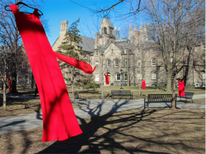 Red dresses hang in the trees outside of the University of Toronto